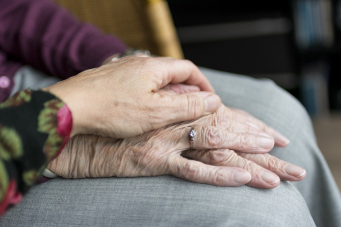 Photo de mains d'une personne âgée en gros plan, avec la main d'une personne aidante posée dessus